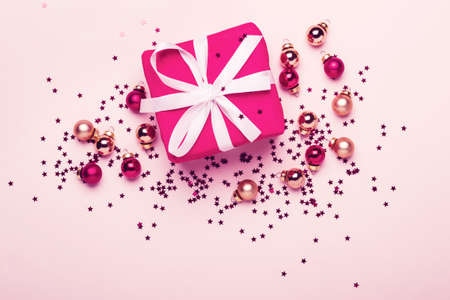 Christmas gift and balls with confetti on pink pastel background.