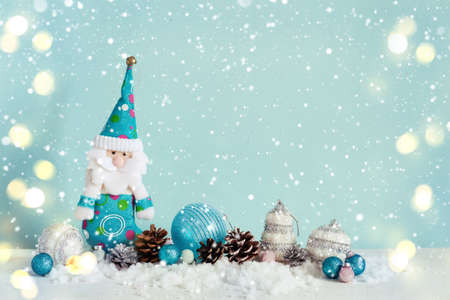 Christmas greeting card with gnome and toys. Blue snow background, bokeh.