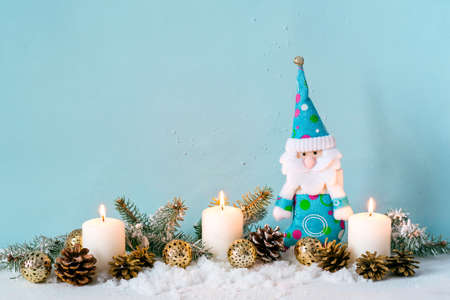 Christmas blue composition. Candles and a dwarf among fir branches Stock Photo