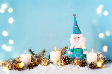 Christmas greeting card with gnome and candles. Blue background, bokeh.