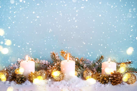 Blue snow Christmas greeting card. Border of fir branches and burning candles.
