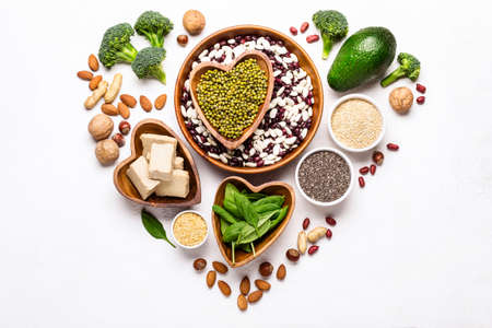 Sources of vegetable protein laid out in the shape of a heart on a white