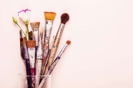 Set of old brushes, flower and palette knife on pale pink background.