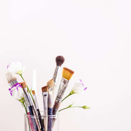 Art brushes and flowers in glass closeup. Selective focus.