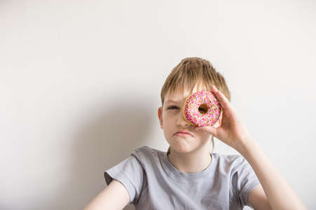 Teen boy looks into glazed donut and funny grimaces. Standard-Bild - 121139448