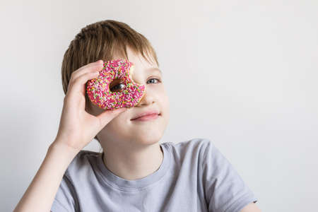 Teen boy looks into hole of bitten donut and funny grimaces. Banco de Imagens
