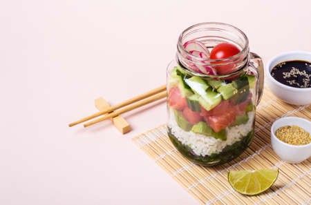 Hawaiian salmon poke salad in glass jar with rice and vegetables.