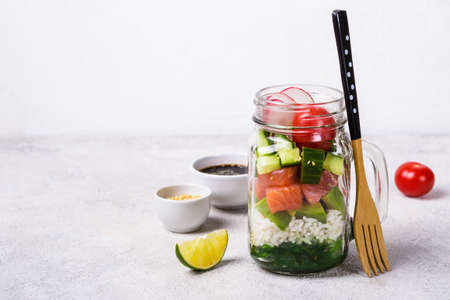 Hawaiian salmon poke salad in glass jar with rice and vegetables on gray background.