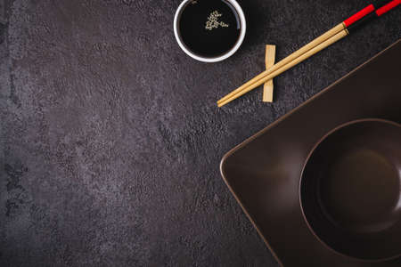 Brown bowls, soy sauce and bamboo chopsticks. Asian table setting.