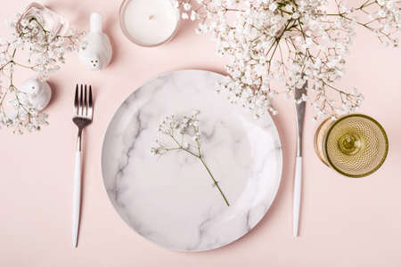 Romantic table setting in pink colors. White flowers decor