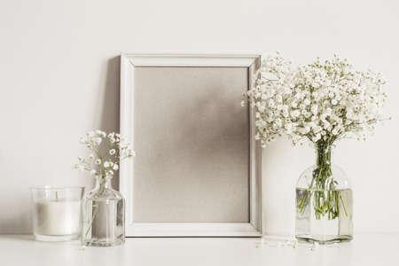 Composición de maqueta con marco de fotos, flores blancas y vela. Foto de archivo