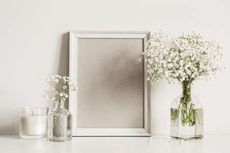 Mockup composition with photo frame, white flowers and candle. 免版税图像