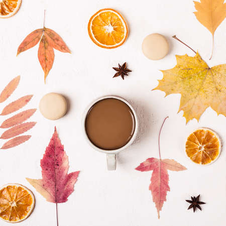 Cup of Coffee and macaroons cookies on white table with autumn leaves pattern.