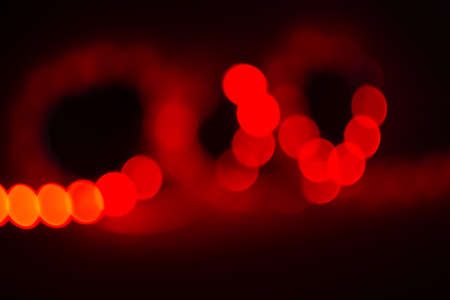 Red neon blurry curls of bokeh lights on black. Abstract background of 80s colors.