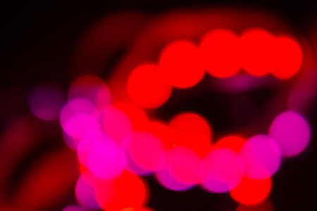 Duotone Red and purple abstraction of blurry neon lights on black.