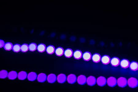 Two neon lines of Violet bokeh lights on black. Abstract background for your design. Reklamní fotografie