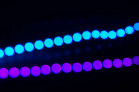 Two duotone neon lines of bokeh lights on black. Abstract background for your design.