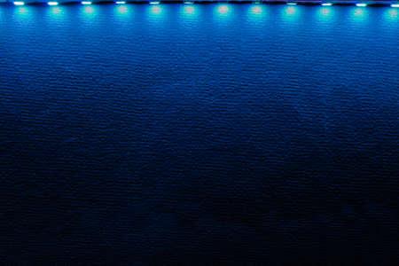 Backlit  of blue led strip lights and reflections on black.