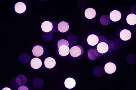Flying violet bokeh lights on black. Holiday concept.