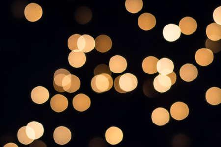 Flying golden bokeh lights on black. Holiday concept.