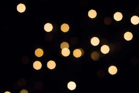 Golden bokeh lights glow on black. Holiday concept.