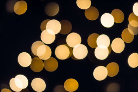 Abstract Golden bokeh lights glow on black. Holiday concept.