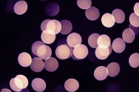 Violet bokeh lights glow on black. Holiday concept.