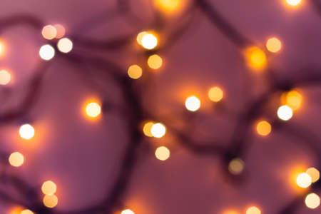 Golden festive bokeh lights on blurred pink