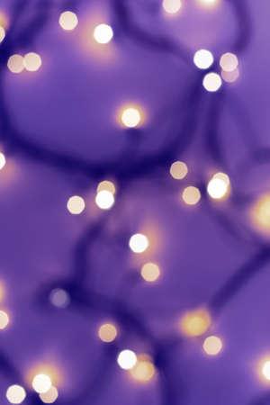 Golden festive bokeh lights on blurred violet