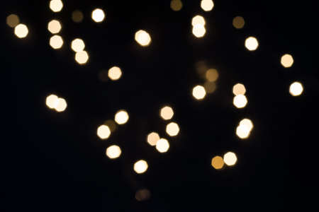 Gold bokeh lights falling on black. Holiday concept.