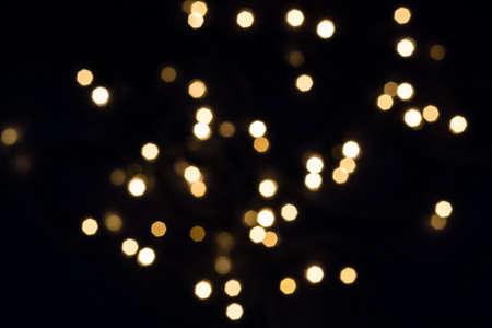 Flying golden bokeh lights in hexagon shape on black. Holiday concept.