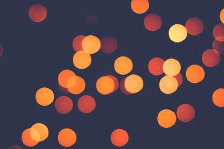 Falling golden bokeh lights on dark. Retro toning.