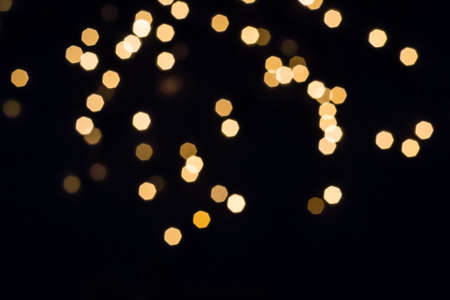 Abstract scattering of golden lights on black
