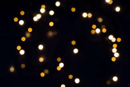 Falling hexagonal bokeh lights on black. Holiday concept.