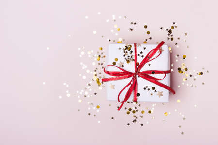 Gift box with red bow and sparkles confetti on pink pastel background. Festive concept. Reklamní fotografie