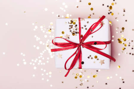 Festive gift box and golden confetti on pink pastel