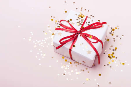 Festive gift box and golden stars sparkles on pink pastel