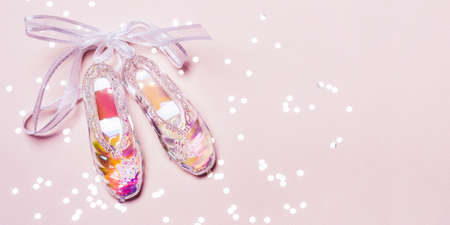Transparent Holographic Christmas Toy Pointer Shoes and sparkle confetti on pink pastel Reklamní fotografie