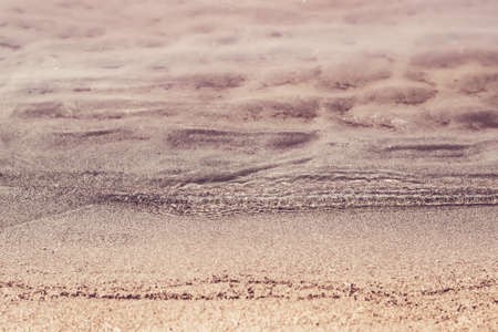 Silent transparent waves and sandy beach close-up. Summer and travel concept.