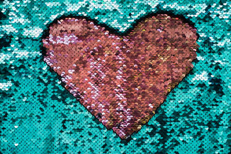 Coral heart made of sequins on turquoise