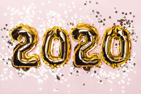 Golden foil balloons 2020 and sparkles on pink pastel