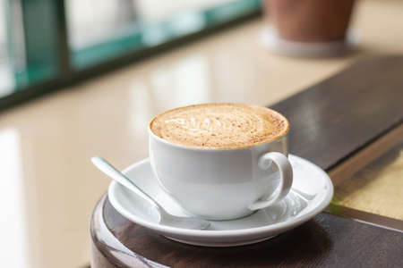 White Cup of Cappuccino with latte art. Coffee on wooden table next to cafe window.