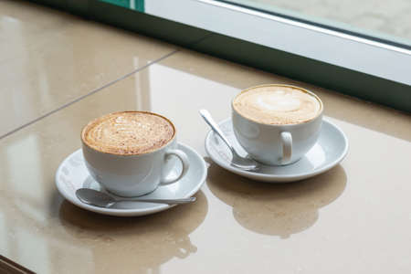 Two Cup of Cappuccino with beautiful crema. Latte art, selective focus. Coffee next to cafe window. Imagens