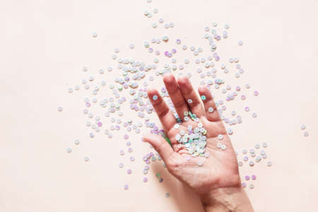 Holographic pastel glitter confetti in female hand on pink Imagens