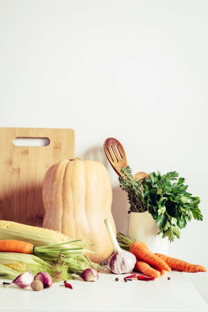 Autumn vegetables and kitchen utensils on table wall