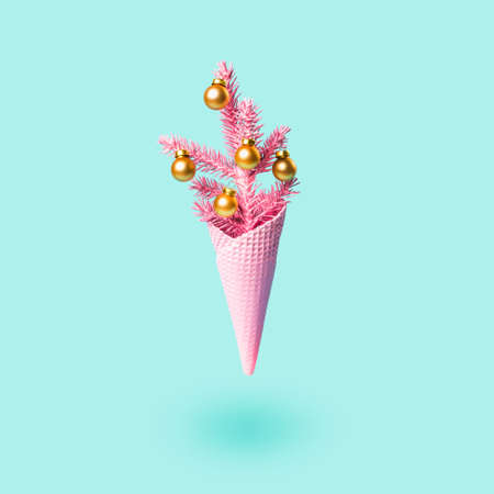 Soaring Painted pink ice cream cone with christmas tree and golden balls. Minimal holiday concept. Modern greeting card.
