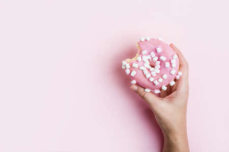 Female hand holding pink bitten donut over pink