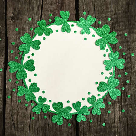 Round frame of shiny shamrocks and confetti. St. Patricks Day background.