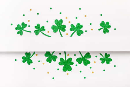 Green glitter shamrocks pattern on white