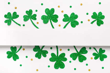 Happy St. Patricks Day minimal background. Green glitter shamrocks border on white background.